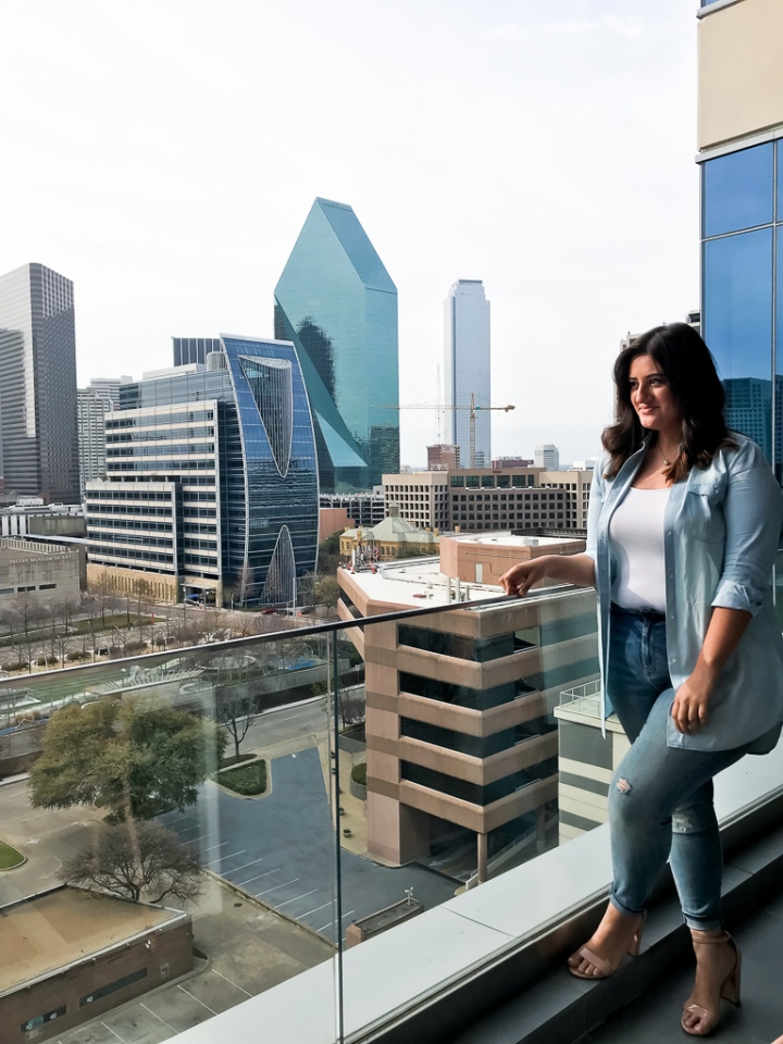 canadian tuxedo with light denim shirt and light washed jeans with white tank top and steve madden heels with dallas skyline backdrop